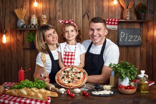 Família feliz em aventais sorrindo e segurando pizza cozida