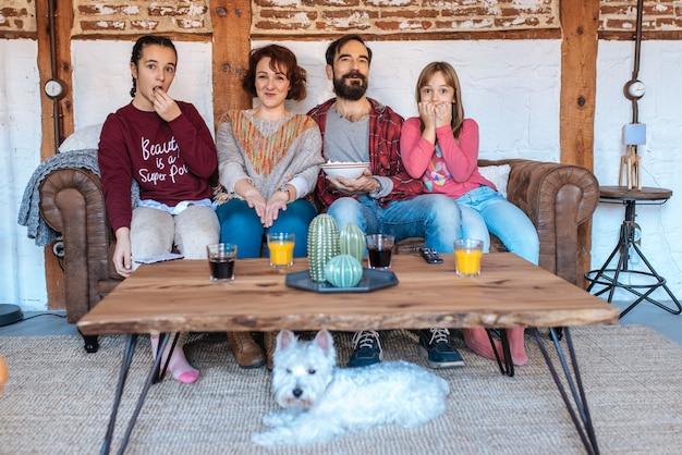 Família feliz em casa assistindo filmes no sofá e comendo pipoca