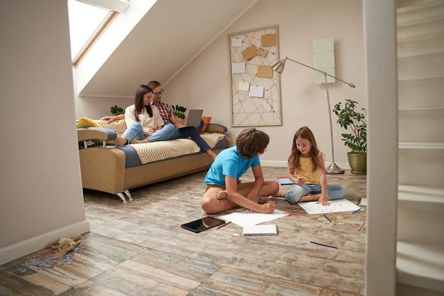 Família feliz em casa, jovem mãe e pai relaxando no sofá e assistindo filme no laptop enquanto