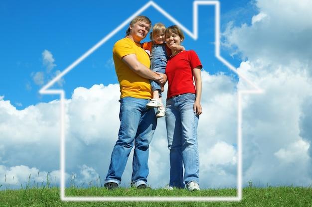 Família feliz em casa na grama verde sob o céu com nuvens