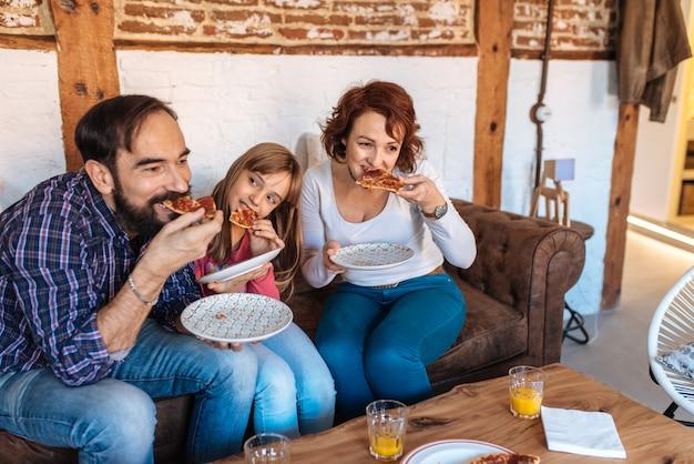 Família feliz em casa no sofá comendo pizza