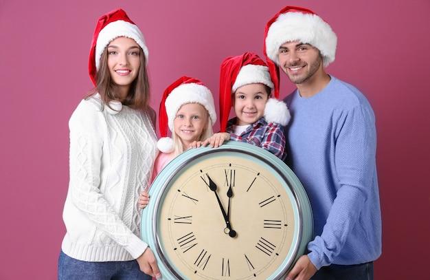 Família feliz em chapéus de papai noel com relógio na parede de cor. conceito de contagem regressiva de natal