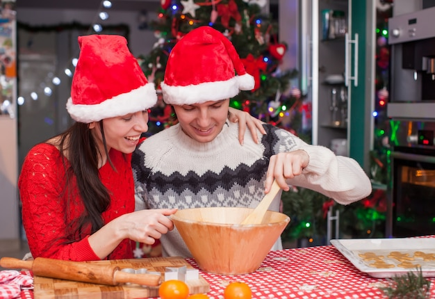 Família feliz em chapéus de papai noel juntos a assar biscoitos de gengibre de natal