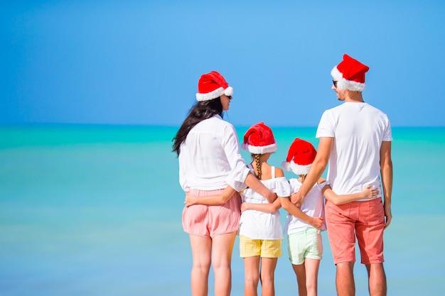Família feliz em chapéus vermelhos de papai noel em uma praia tropical, comemorando as férias de natal