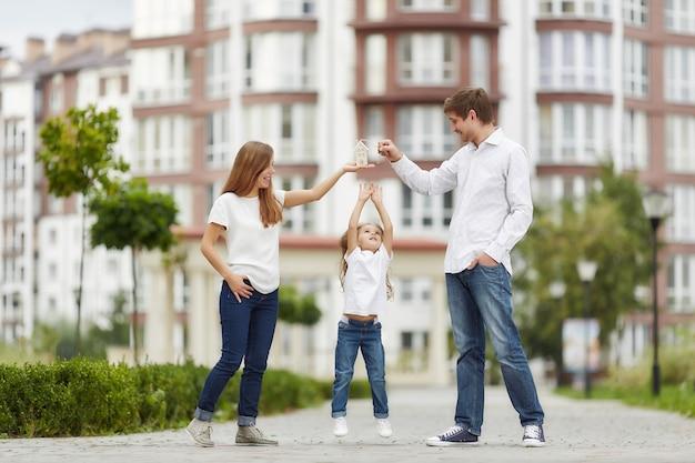 Família feliz em frente ao novo prédio de apartamentos