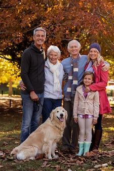 Família feliz em pé com cachorro no parque