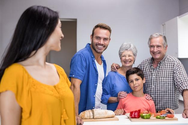 Família feliz em pé na cozinha