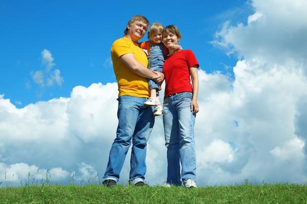 Família feliz em pé na grama verde sob o céu com nuvens