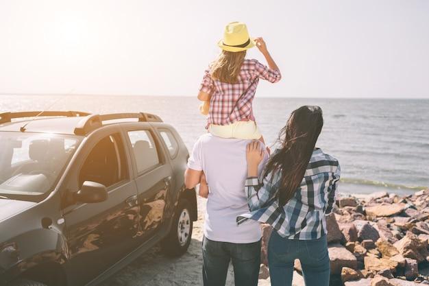 Família feliz em pé perto de um carro na praia. família feliz em uma viagem em seu carro. pai, mãe e filha estão viajando pelo mar ou pelo oceano ou pelo rio. passeio de verão de automóvel