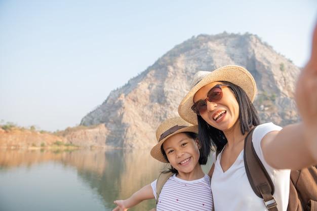 Família feliz em pé perto do lago