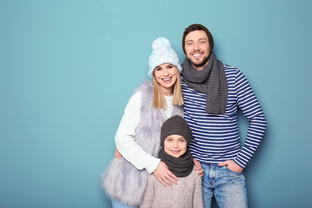 Família feliz em roupas quentes na cor de fundo. pronto para as férias de inverno