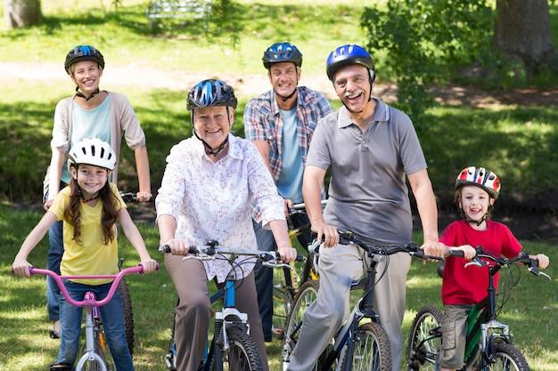 Família feliz em sua bicicleta no parque em um dia ensolarado