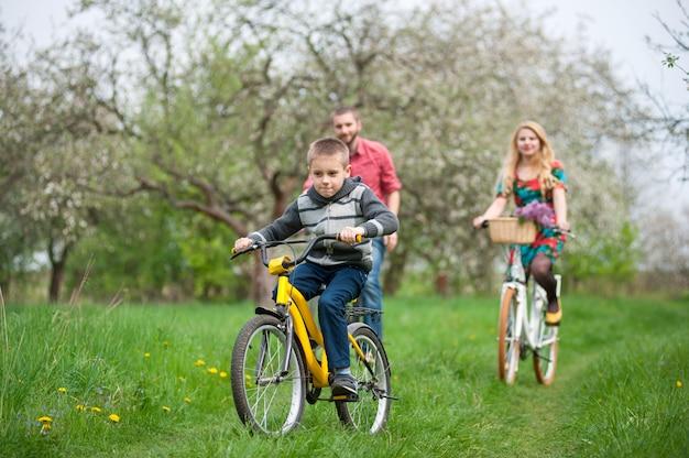Família feliz em um bicicletas no jardim primavera