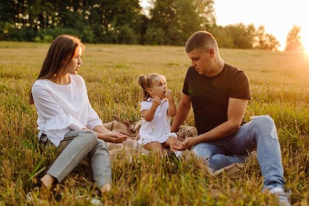 Família feliz em um campo no outono. mãe, pai e bebê brincam na natureza sob os raios do pôr do sol