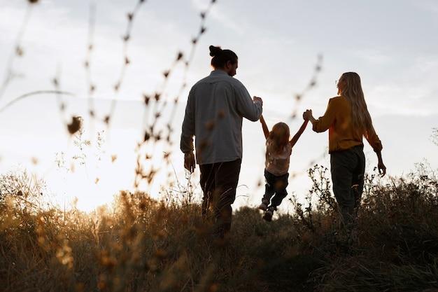 Família feliz em um passeio ao pôr do sol à noite