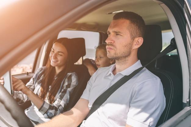 Família feliz em uma viagem em seu carro. pai, mãe e filha estão viajando pelo mar ou pelo oceano ou pelo rio. passeio de verão de automóvel