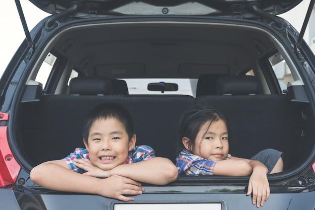 Família feliz em uma viagem, sentado no tronco do carro