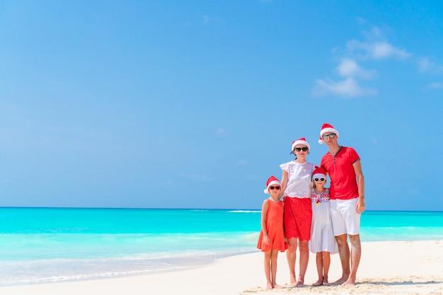 Família feliz, em, vermelho, chapéus santa, ligado, um, praia tropical, celebrando, natal, férias