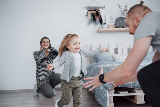 Família feliz está se divertindo em casa. mãe, pai e filha com brinquedos de pelúcia estão gostando de estar juntos