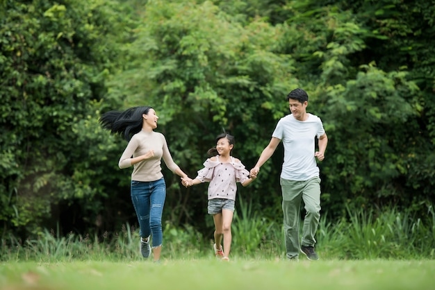 Família feliz está se divertindo mãe, pai e filha estão correndo no parque.