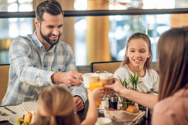 Família feliz. família feliz tomando café da manhã juntos e parecendo animada