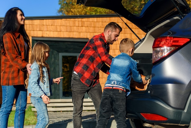 Família feliz fazendo as malas no porta-malas de um carro antes de se mudar para uma nova casa ou ir de férias