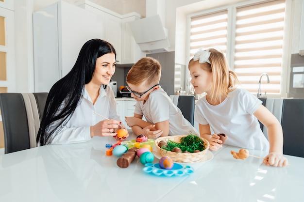 Família feliz fazendo decorações para as férias da páscoa