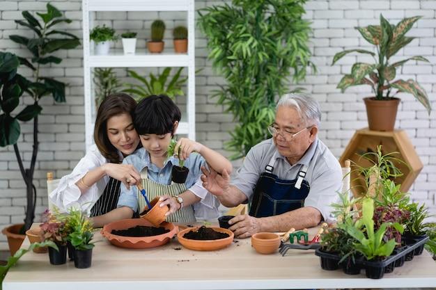 Família feliz fazendo jardinagem no jardim, avô, neto e mulher cuidando da natureza