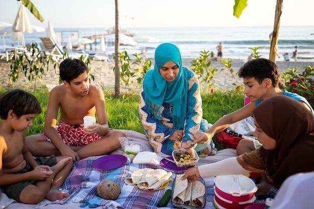 Família feliz fazendo piquenique na praia perto do mar