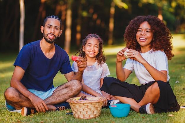Família feliz fazendo piquenique no parque
