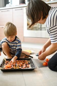 Família feliz fazer comida em casa. mãe juntos sua criança de filho de quatro anos criança cozinhar pizza na cozinha.