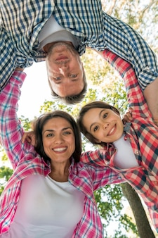 Família feliz formando amontoado no parque contra o céu