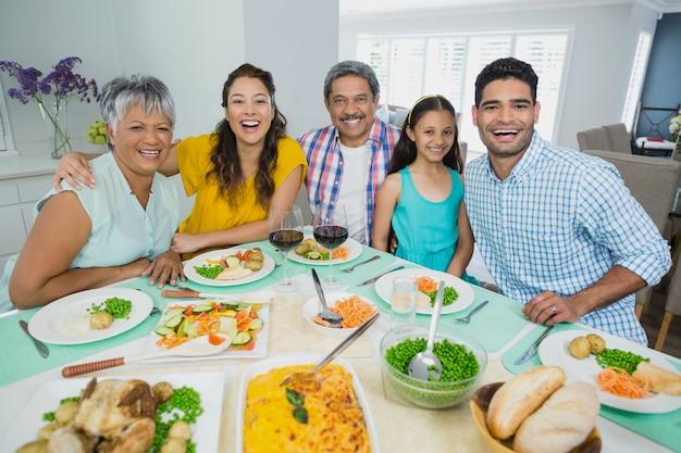 Família feliz geração multi, tendo a refeição na mesa em casa