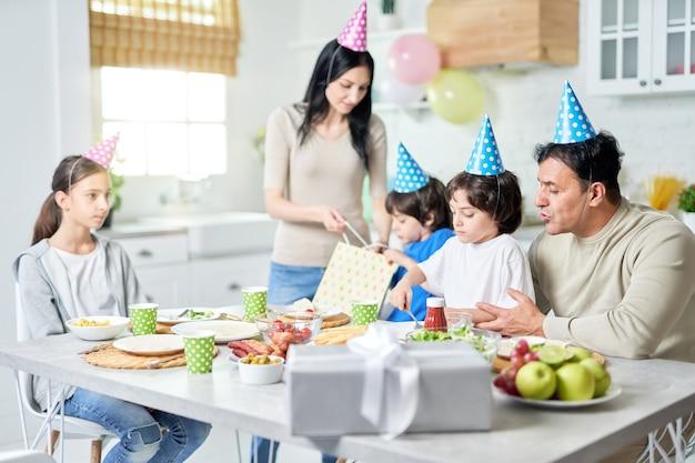 Família feliz hispânica jantando enquanto comemorava aniversário juntos em casa. paternidade, conceito de celebração. foco seletivo