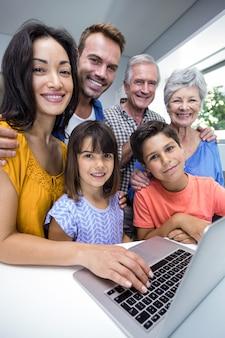 Família feliz interagindo usando laptop