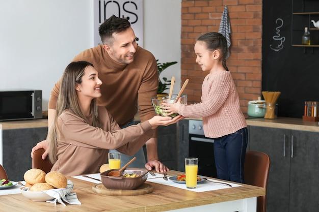 Família feliz jantando juntos na cozinha
