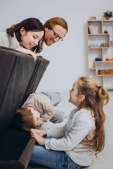 Família feliz jogando e se divertindo juntos no sofá