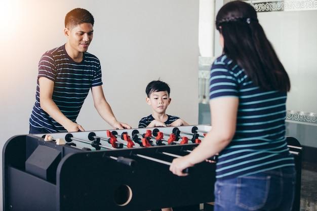 Família feliz jogando futebol de mesa para relaxar de férias em casa