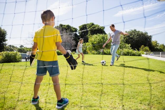 Família feliz jogando futebol no parque