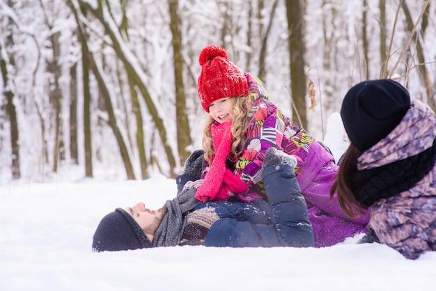 Família feliz jogando na floresta de inverno