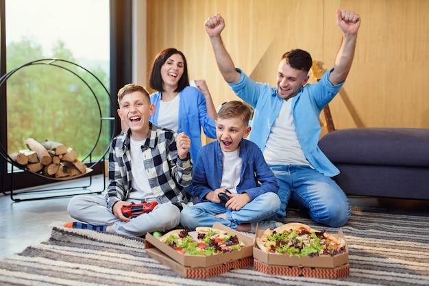 Família feliz jogando videogame com gamepads e comendo uma pizza saborosa