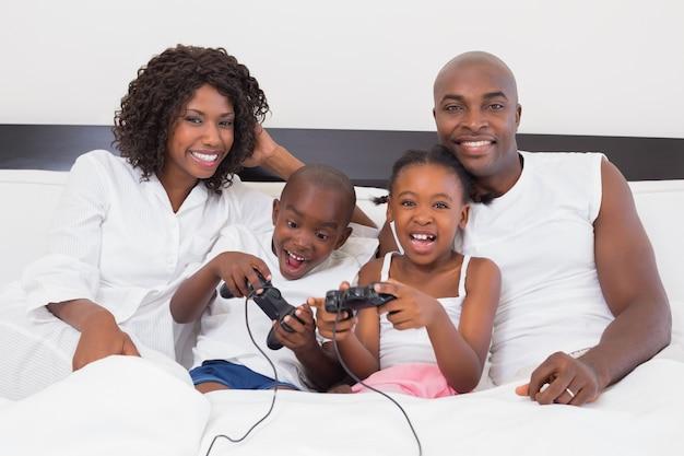 Família feliz jogando videogames juntos na cama