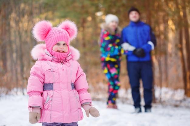 Família feliz, jovem casal e sua filha passar tempo ao ar livre no inverno