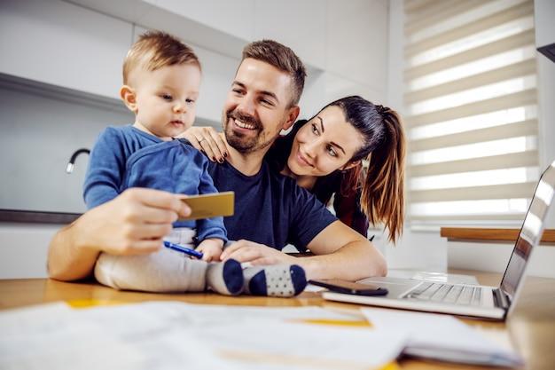 Família feliz jovem comprando coisas para casa. mulher está abraçando o marido, a criança está sentada na mesa de jantar e o marido segurando um novo cartão de débito. compras online.