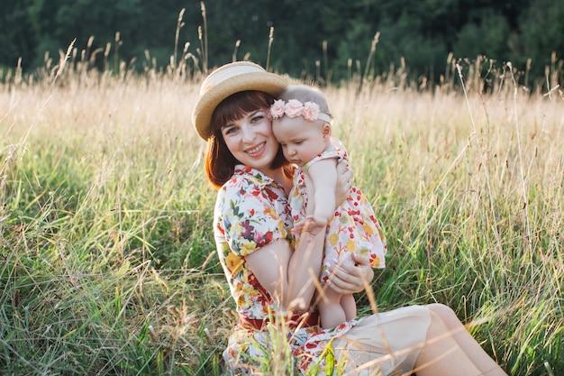 Família feliz, jovem mulher bonita sentada na grama com sua filha bonita no campo em um dia ensolarado de verão. relacionamento de pais e filhos. conceito do dia das mães