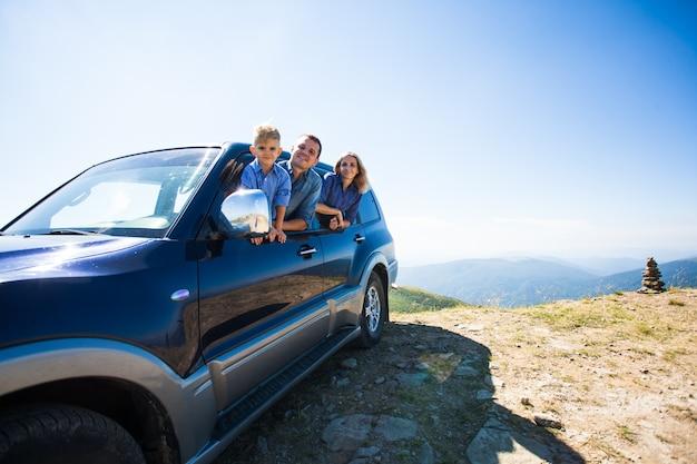 Família feliz, jovem pai, mãe e filho, olhando para fora do carro durante a viagem