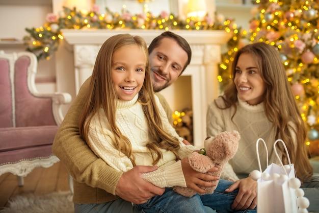 Família feliz. jovens pais dando um presente de natal para sua filha e família parecendo felizes