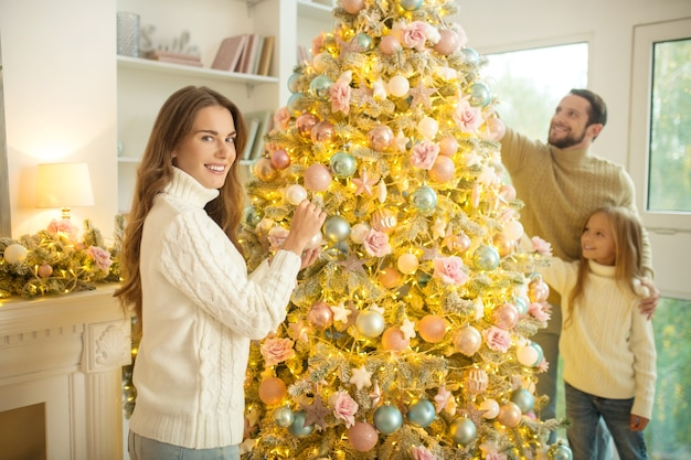 Família feliz. jovens pais e sua filha decorando uma árvore de natal