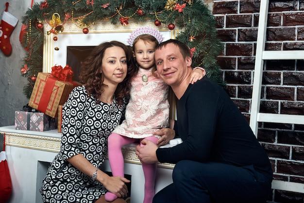 Família feliz junto à lareira para as férias de inverno. véspera de natal e véspera de ano novo.