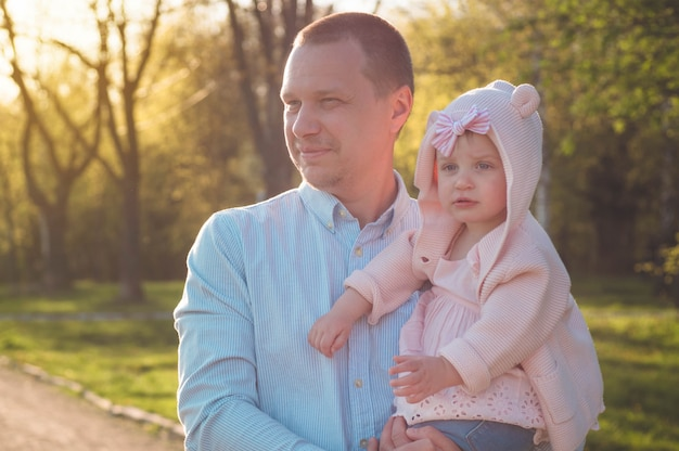 Família feliz junto, pais com seu filho pequeno ao pôr do sol. pai levantando bebê no ar. conceito de dia dos pais